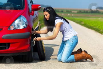 woman changing her own tire